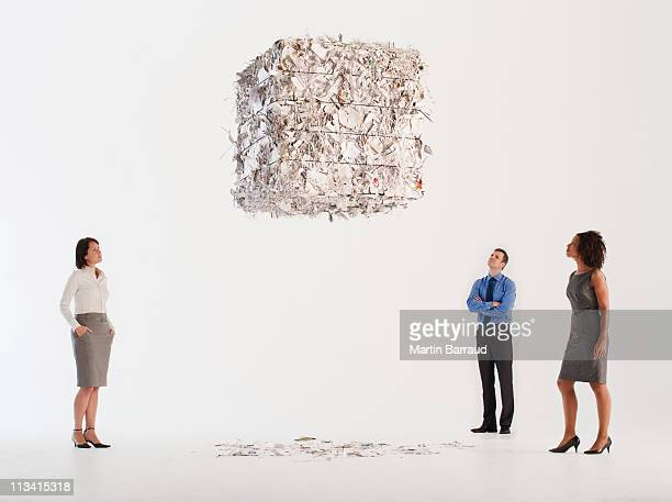 Business people looking at floating paper bale