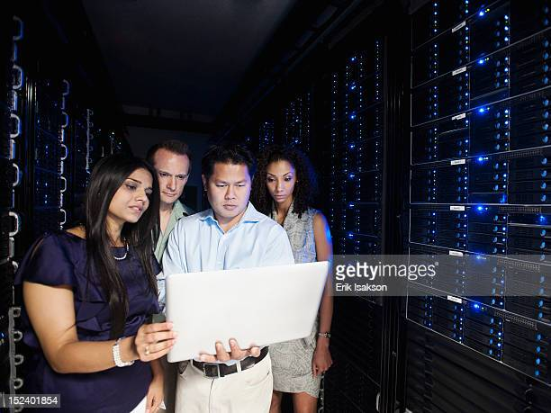 Business people looking at laptop in server room