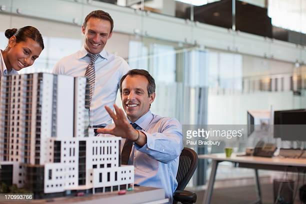 Geschäftsleute, die ein Modell Haus im Büro