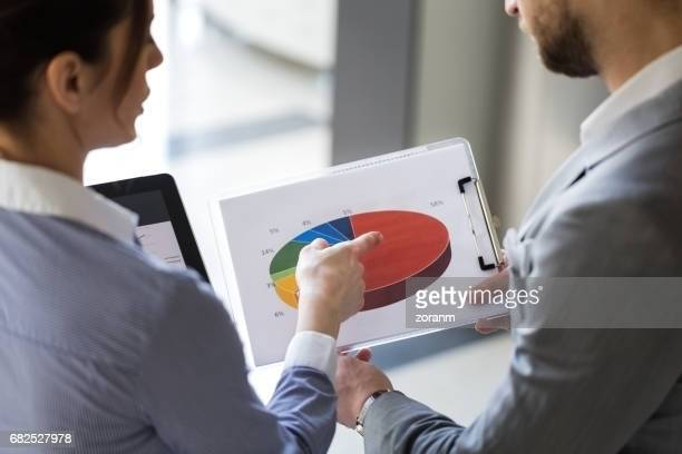 Business people looking at pie chart