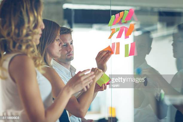 Business people looking at sticky notes and writing.