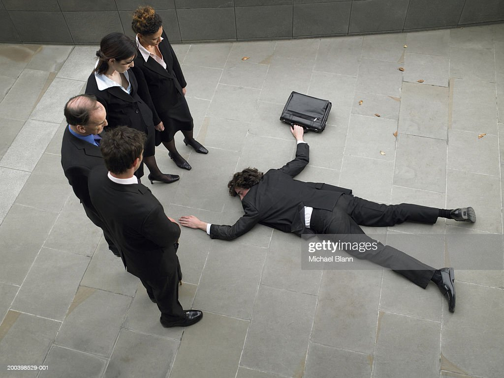 Business people looking down at man lying on pavement, elevated view : Stock Photo