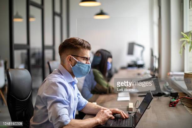 business people maintaining social distance while working in office - employee stock pictures, royalty-free photos & images