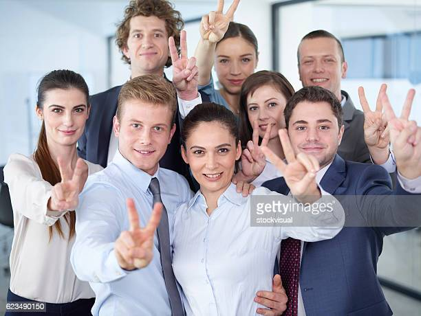 Business people make victory sign