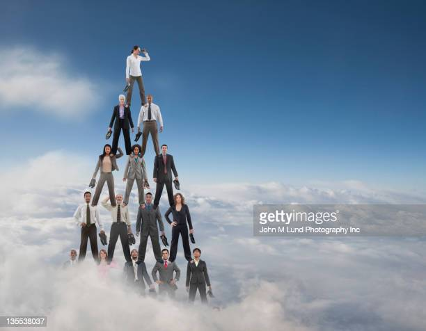 business people making a human pyramid - pyramid stock pictures, royalty-free photos & images