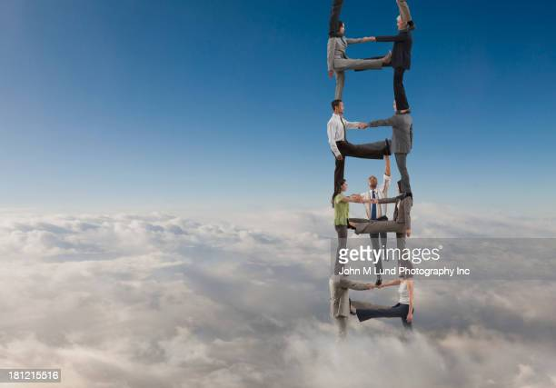 Business people making ladder for colleague