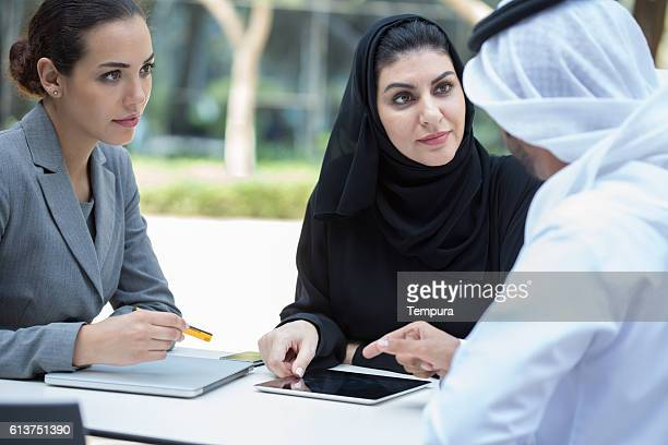 Business people meet outdoors in Dubai.