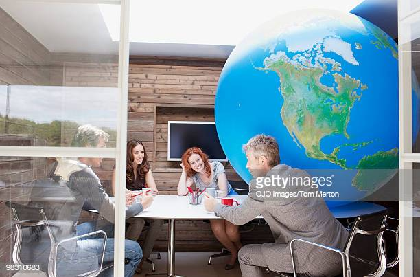 Business people meeting at conference table with large globe