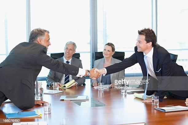 Hommes d'affaires réunis autour d'une table dans la salle de conférence