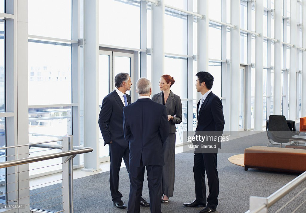 Business people meeting at window in office lobby : Stock Photo