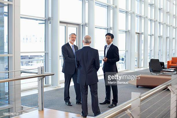 Business people meeting at window in office lobby