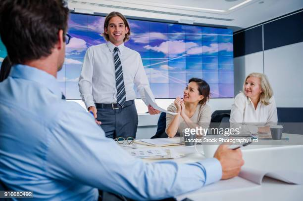 Business people meeting in conference room with visual screen