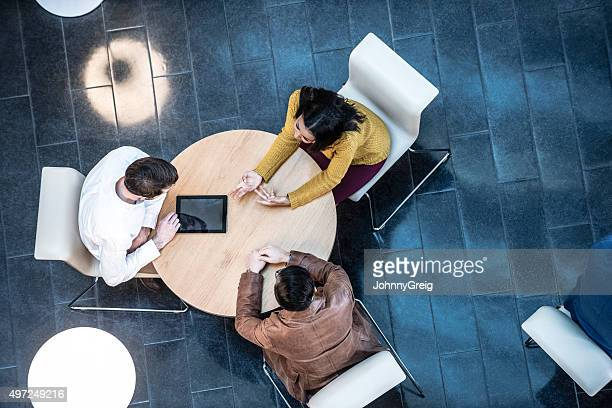 business people meeting in modern office, view from above - three people stock pictures, royalty-free photos & images