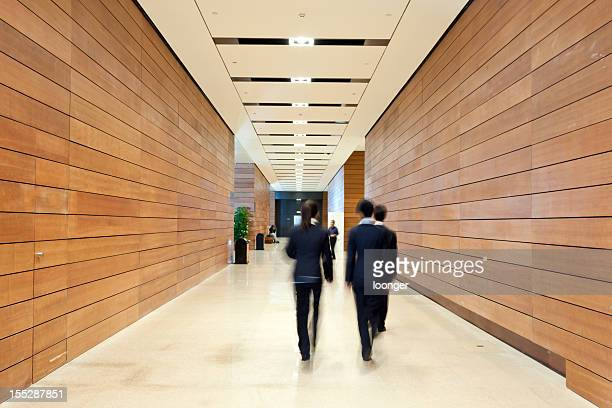 business people moving along the corridor - ceiling stock pictures, royalty-free photos & images
