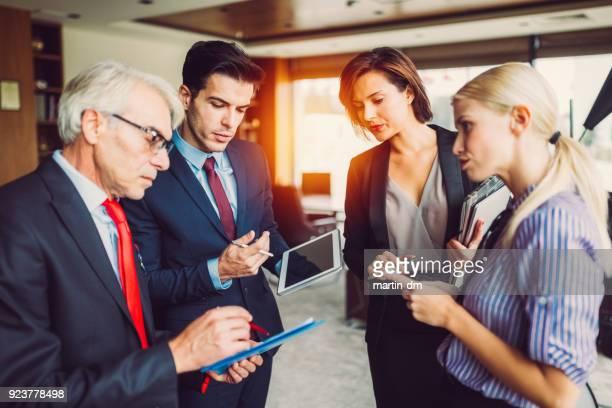 Business people multi-tasking in group