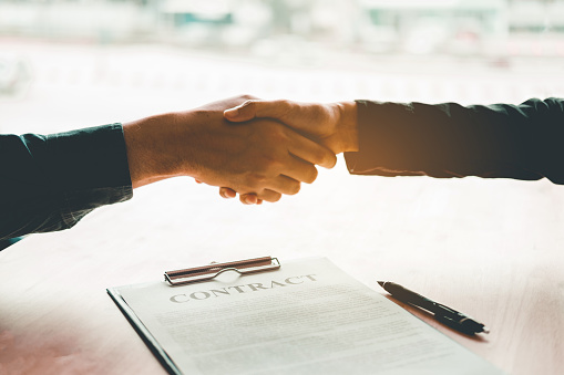 Business people negotiating a contract handshake between two colleagues 937138664