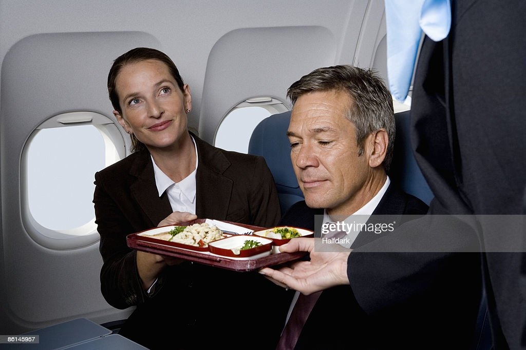 Business people on a plane being served airline food : Stock Photo