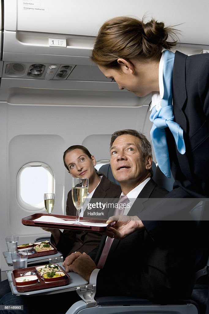 Business people on a plane being served meals and champagne : Stock Photo