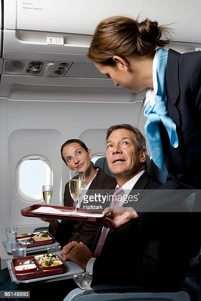 Business people on a plane being served meals and champagne