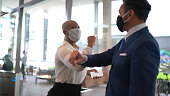 Business people on a safety greeting for covid-19 on office's lobby - with face mask