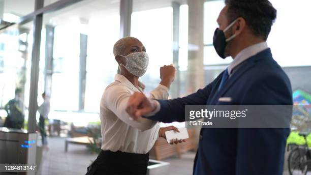business people on a safety greeting for covid-19 on office's lobby - with face mask - arrival stock pictures, royalty-free photos & images