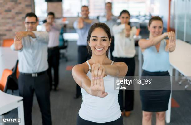 business people on an active break at the office - stretching stock photos and pictures