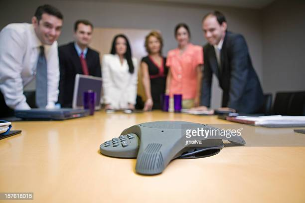 Business people on conference call around phone and table