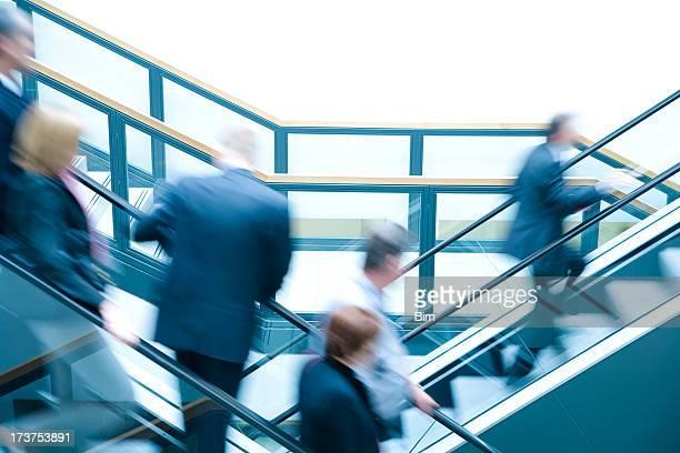 Business people on escalators, blurred motion