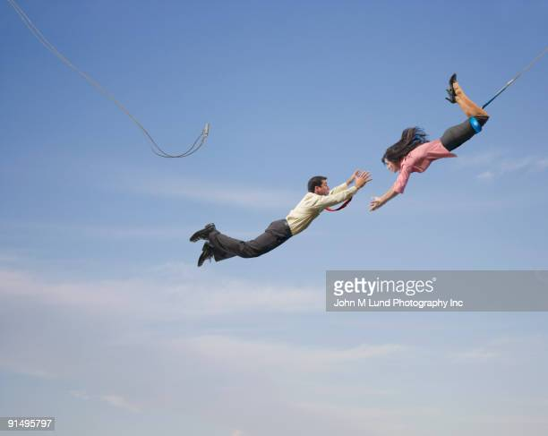 business people on flying trapeze - trust stock pictures, royalty-free photos & images