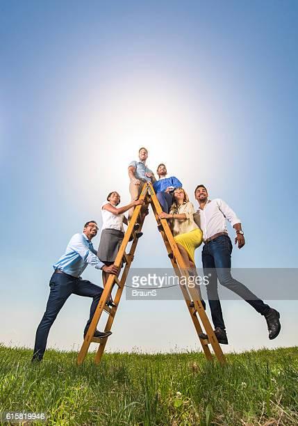 Empresários em escadas de sucesso contra o céu.