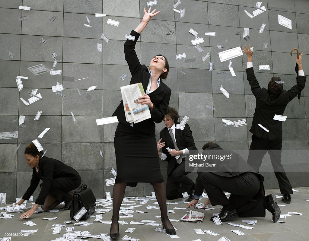 Business people on pavement catching falling money : Stock-Foto