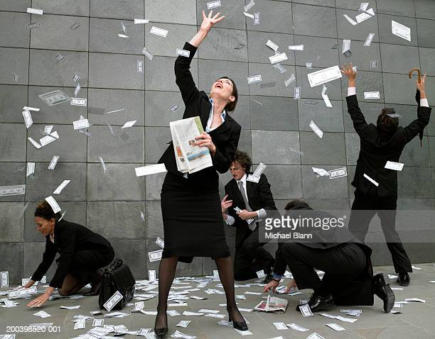 business people on pavement catching falling money - prosperity stock pictures, royalty-free photos & images
