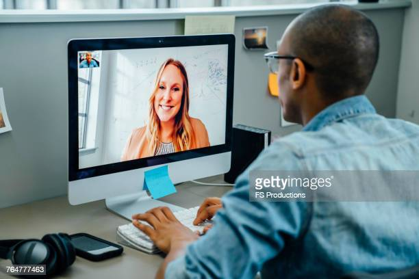 business people on video conference - over the shoulder view stock pictures, royalty-free photos & images