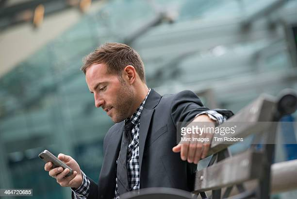 Business people out and about in the city. A man in a business suit. A man with short red hair and a beard, wearing a suit, on his phone.