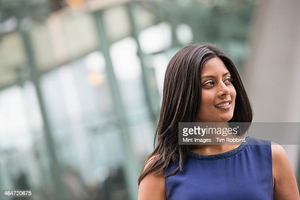 Business people out and about in the city. A woman with long black hair wearing a blue dress.