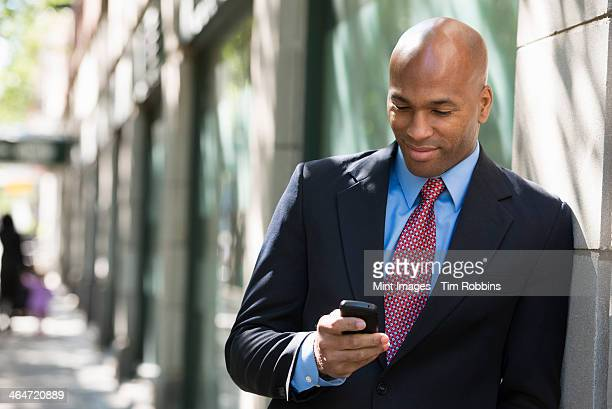 Business people outdoors, keeping in touch while on the go. A businessman in a suit and red tie, checking his phone.