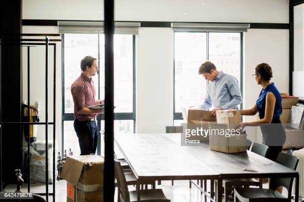 Business people packing boxes at table in office