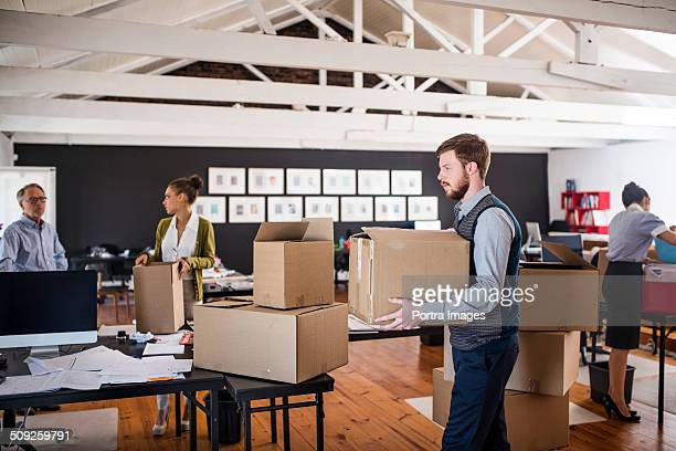 Business people packing cardboard boxes in office