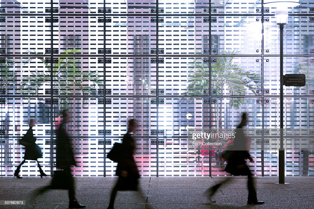 Business people passing modern office building : Stock Photo