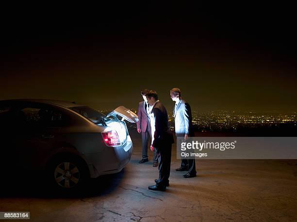Business people peering into open glowing car trunk