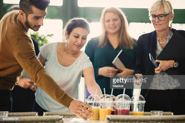 Business people picking up disposable cups of fresh juice in office