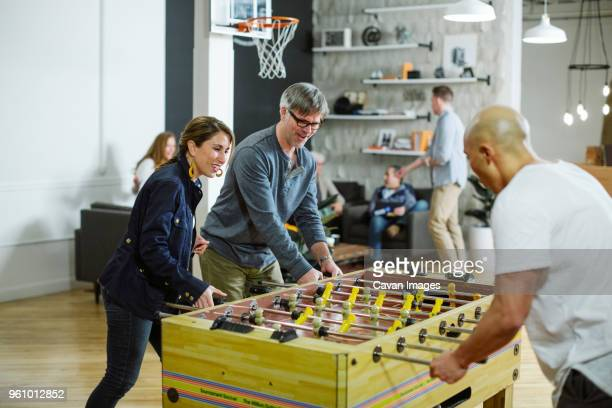Business people playing foosball in office
