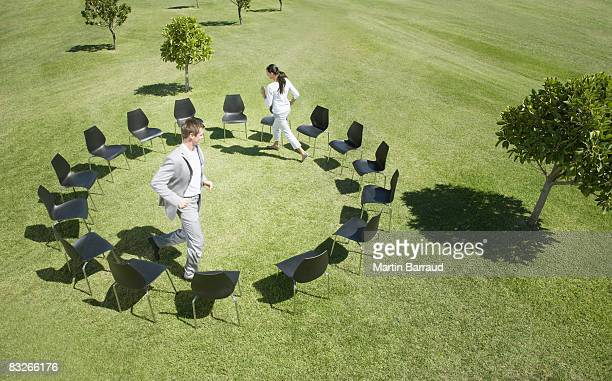 Business people playing musical chairs in field