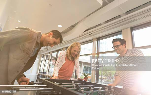 Business people playing table football in office