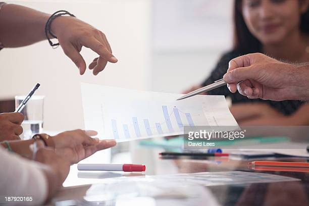 Business people pointing at graph in meeting