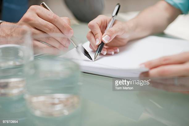 Geschäftsleute zeigt auf Papierkram und Stifte