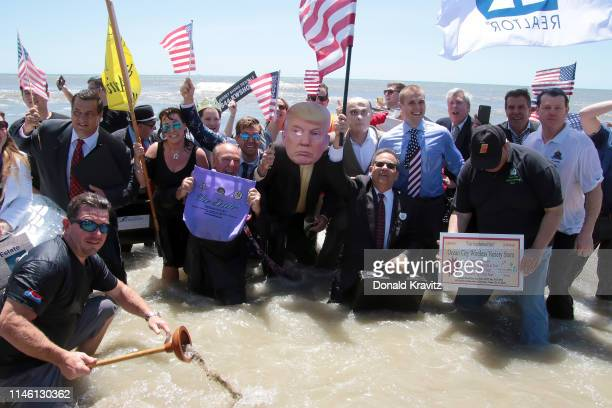 """Business people pose for a photograph in the ocean while participating in the """"Business Persons Plunge"""" May 24, 2019 in Ocean City, New Jersey."""