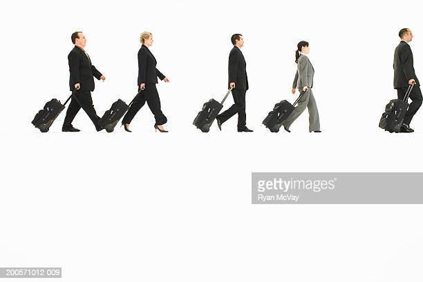 Business people pulling suitcases in studio