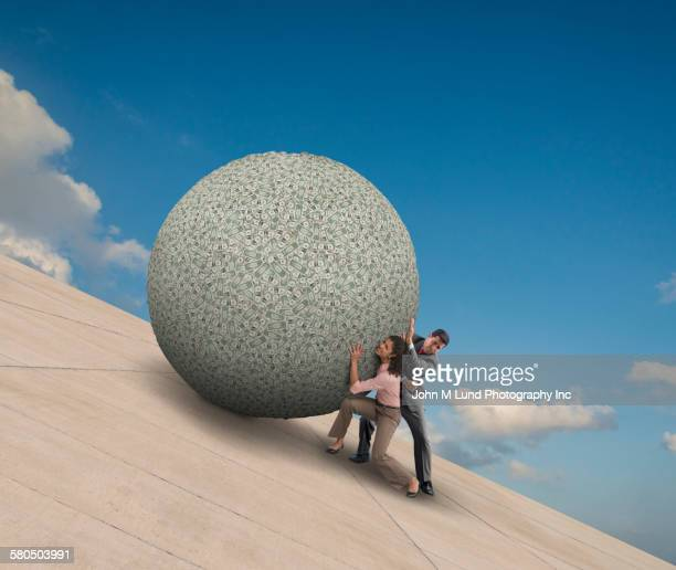 Business people pushing boulder on slope