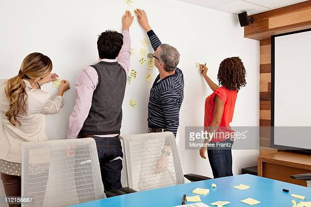 Business people putting adhesive notes on conference room wall